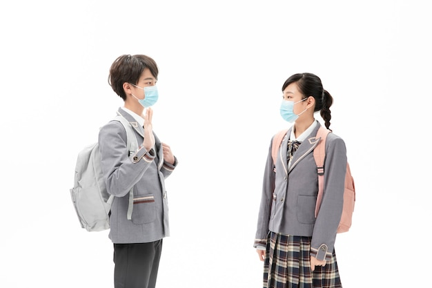 Crianças com máscara em uniforme escolar