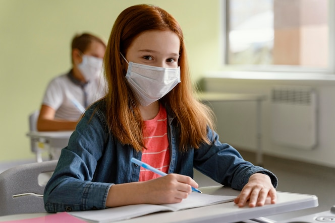 Crianças com máscaras médicas estudando na escola