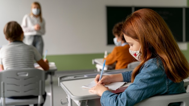Crianças com máscaras médicas frequentando a escola