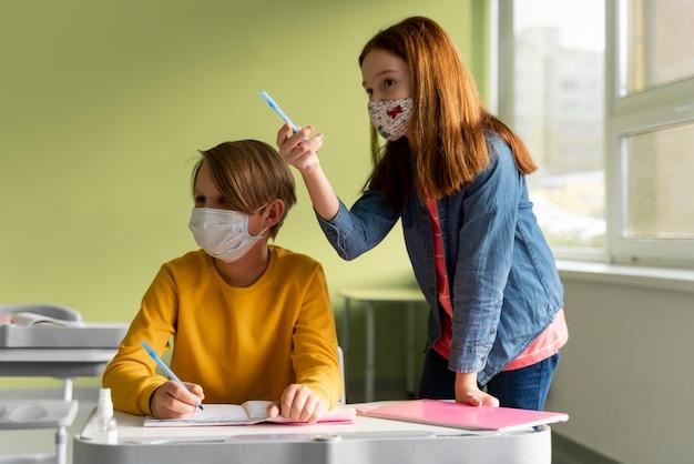 Crianças com máscaras médicas na escola, frequentando as aulas