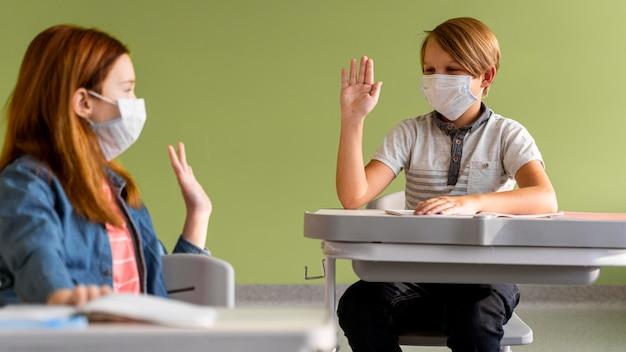 Crianças com máscaras médicas se cumprimentando à distância