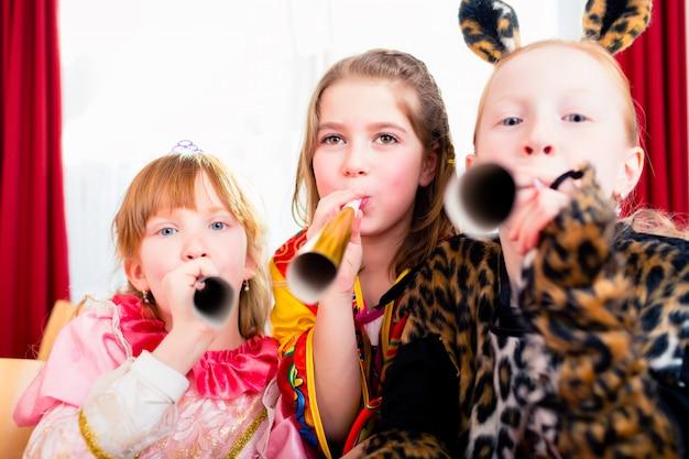 Crianças com noisemakers fazendo barulho na festa