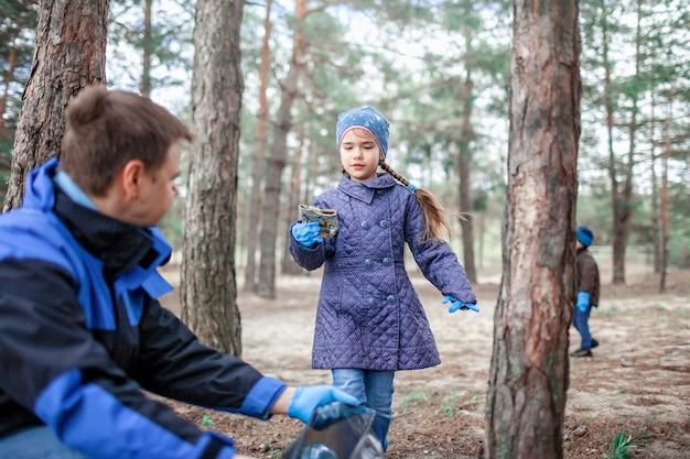 Crianças com o pai, limpando a área na floresta perto da praia