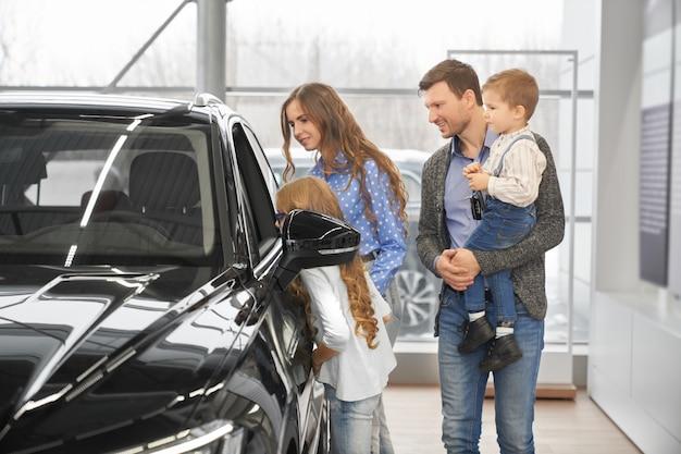 Crianças com pais olhando para salão de automóvel através da janela