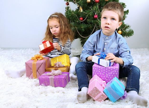 Crianças com presentes perto da árvore de natal no quarto