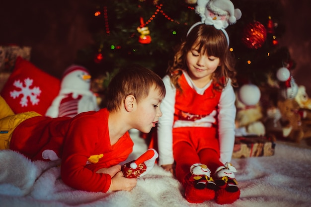 Crianças com roupas vermelhas sentam-se diante de uma árvore de natal
