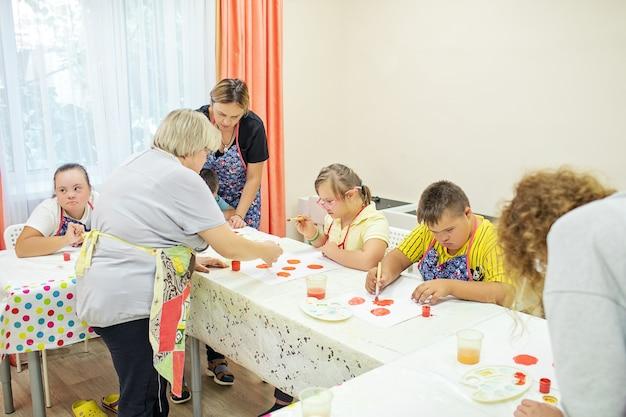 Crianças com síndrome de down desenham em uma mesa