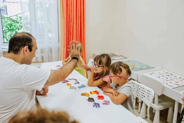 Crianças com síndrome de down estudando e brincando na sala com carteiras brancas