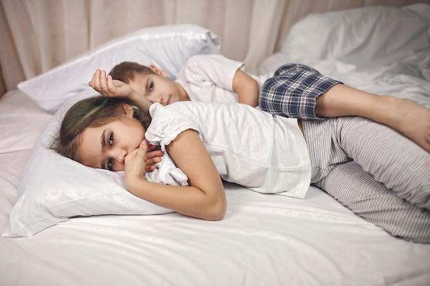 Crianças com sono de pijama deitadas na cama e lutando para dormir à noite