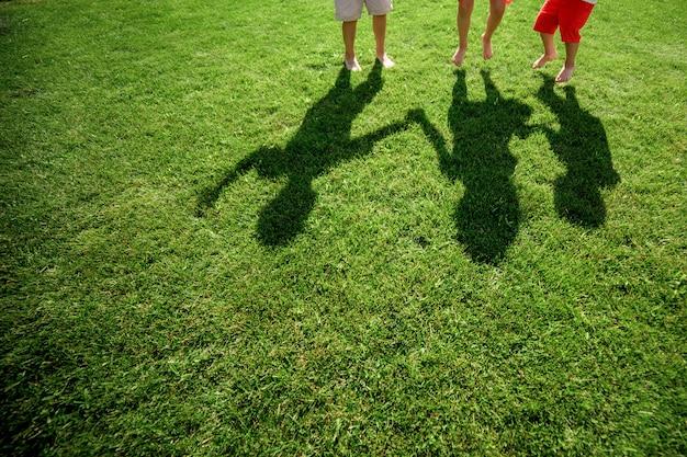 Crianças com suas sombras na grama. silhuetas de três pessoas em pé com as mãos esticadas