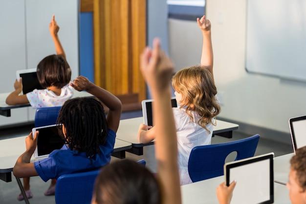 Crianças com tablets digitais levantando as mãos