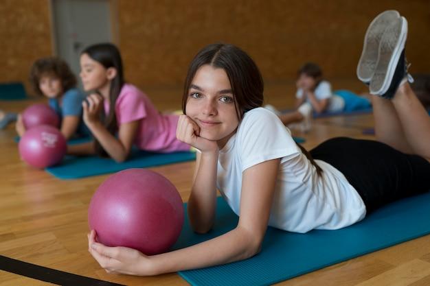 Crianças com tiro médio em tapetes de ioga