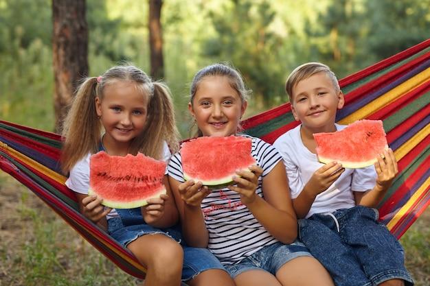 Crianças comem melancia e brincam, ao ar livre, sentadas na rede