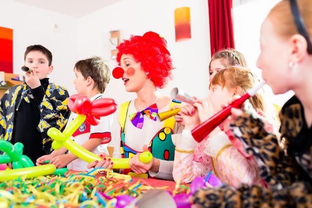 Crianças comemorando festa de aniversário com fazedores de barulho enquanto um palhaço está visitando e entretendo as crianças
