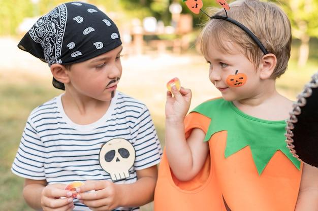 Crianças comemorando o dia das bruxas ao ar livre