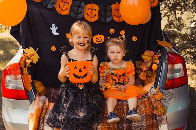Crianças comemorando o dia das bruxas no porta-malas do carro