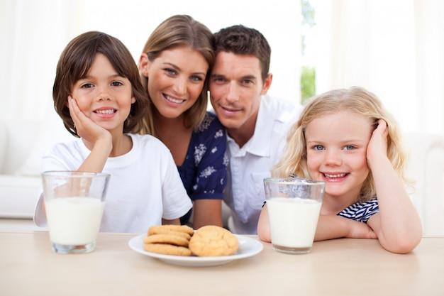 Crianças comendo biscoitos e dinking leite com seus pais