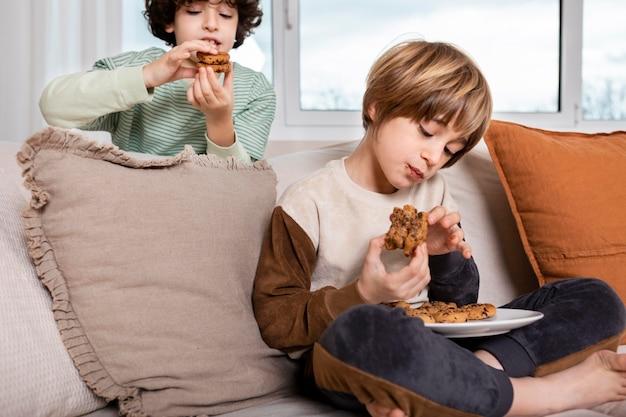 Crianças comendo biscoitos em casa