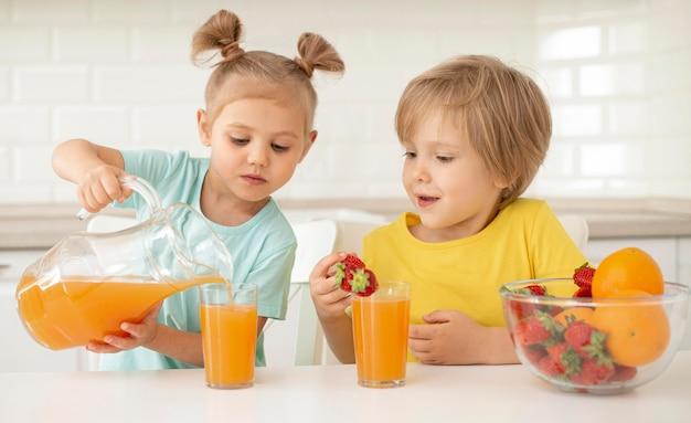 Crianças comendo frutas e bebendo suco