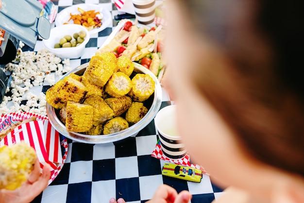 Crianças comendo pipoca durante um aniversário de verão.