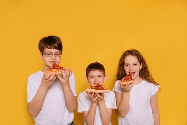 Crianças comendo pizza de pepperony na parede amarela.