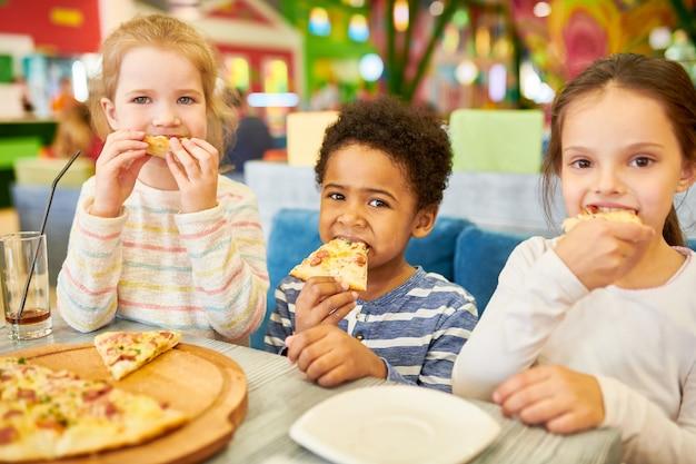 Crianças comendo pizza no café