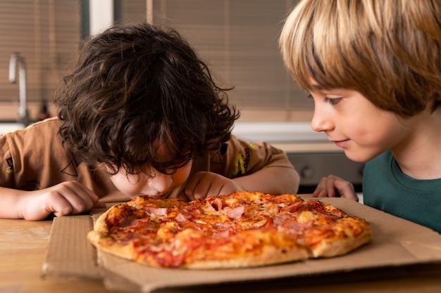 Crianças comendo pizzas juntas
