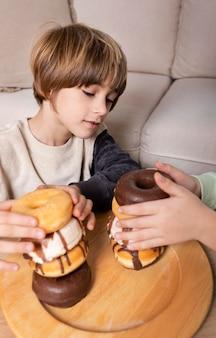 Crianças comendo rosquinhas em casa