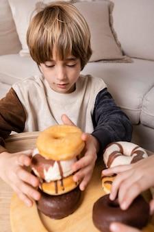 Crianças comendo rosquinhas em casa Foto gratuita