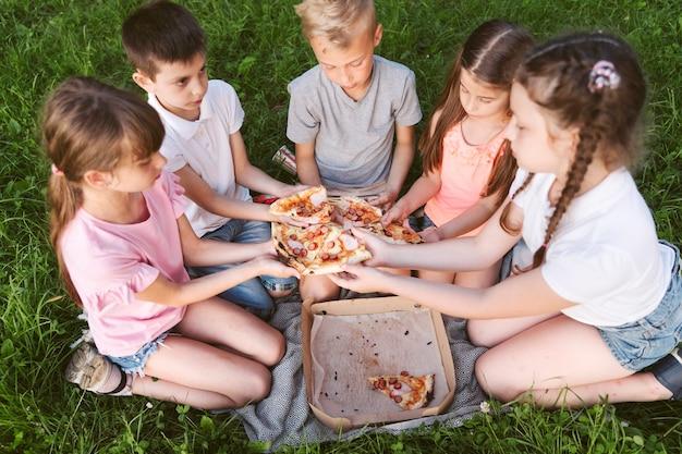 Crianças compartilhando uma pizza juntos