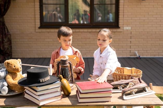 Crianças comprando brinquedo e livro na liquidação de garagem