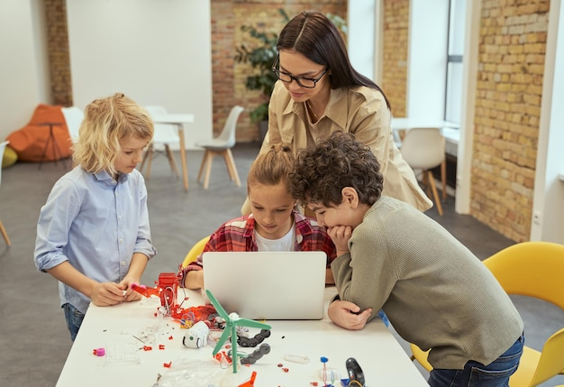 Crianças concentradas no processo aprendem a construir brinquedos robóticos e a programá-los usando