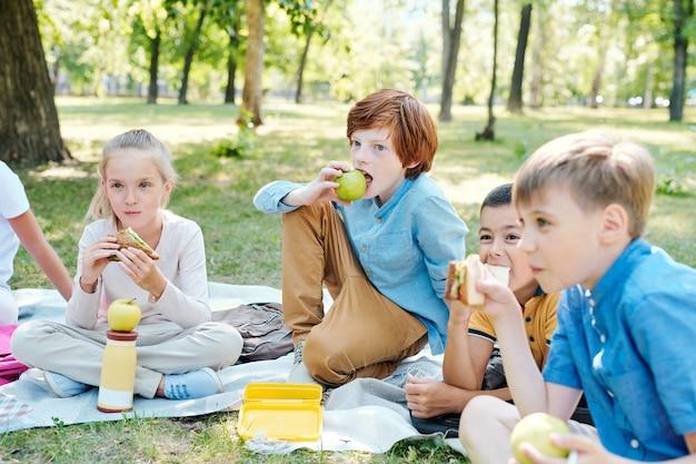 Crianças conversando no parque, segurando o planeta modelo enquanto aproveitam a aula de astronomia ao ar livre sob a luz do sol