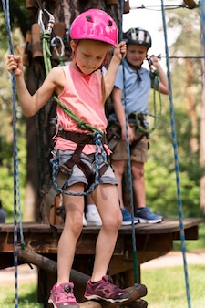 Crianças corajosas se divertindo em um parque de aventura Foto gratuita