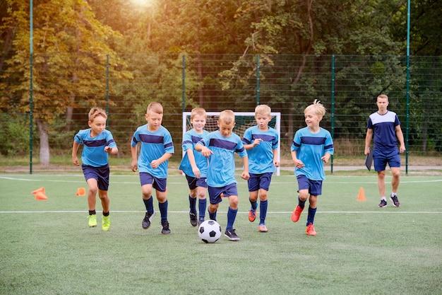 Crianças correndo e chutando bola de futebol na sessão de treinamento de futebol infantil