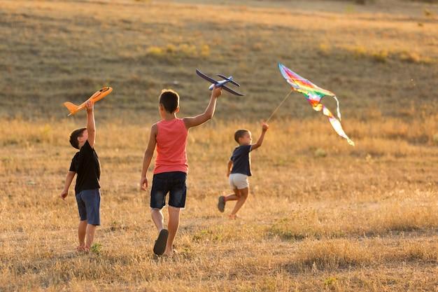 Crianças correndo pelo campo, três meninos lançando aviões de brinquedo e uma pipa