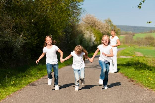 Crianças correndo por um caminho, mãe grávida em pé