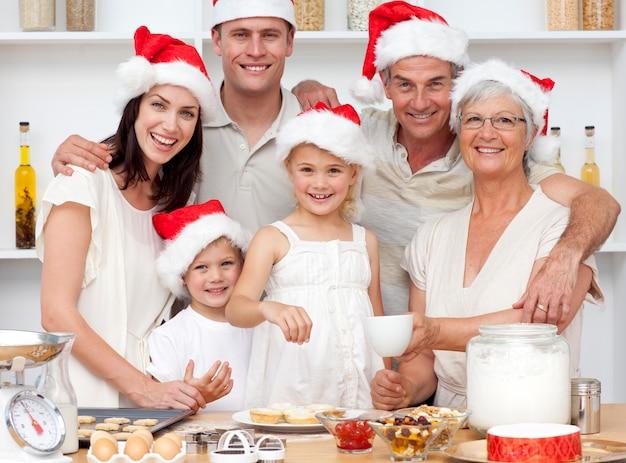 Crianças cozinhando bolos de natal na cozinha com sua família