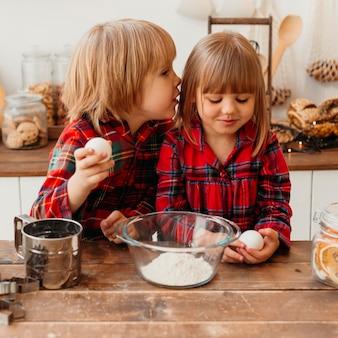 Crianças cozinhando juntas em casa