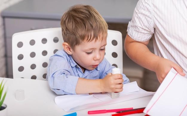 Crianças criam atividades com papel colorido e cola para crianças criativas
