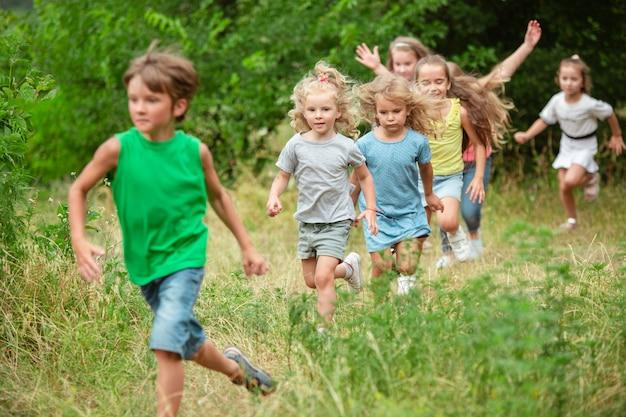 Crianças, crianças correndo em um prado verde, floresta
