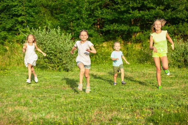 Crianças, crianças correndo na campina sob a luz do sol, felicidade