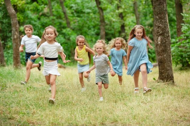 Crianças crianças correndo na floresta do prado verde, infância e verão