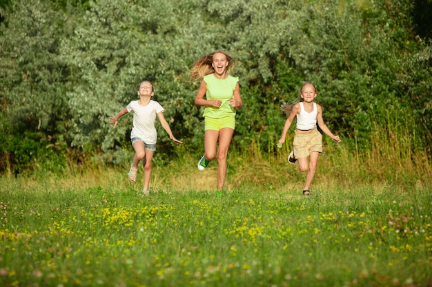 Crianças, crianças correndo no pasto ao sol do verão. pareça feliz, alegre, com emoções brilhantes e sinceras. bonitos meninos e meninas caucasianos. conceito de infância, felicidade, movimento, família e verão.