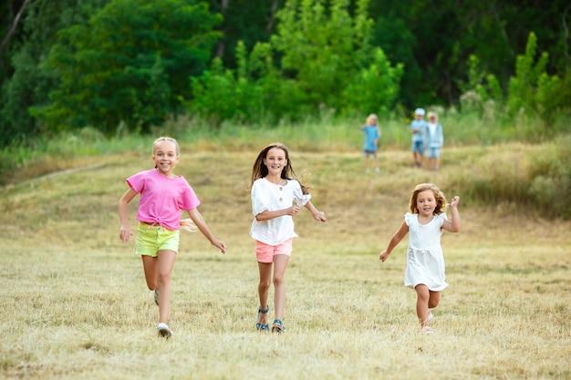 Crianças, crianças correndo no pasto sob o sol do verão. pareça feliz, alegre, com emoções brilhantes e sinceras. bonitos meninos e meninas caucasianos. conceito de infância, felicidade, movimento, família e verão.