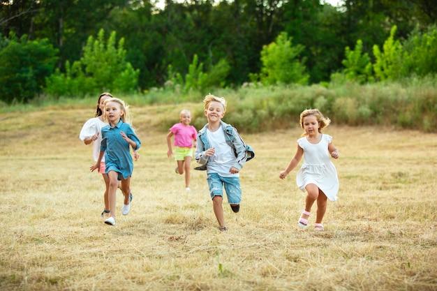 Crianças, crianças correndo no prado, na luz do sol de verão.