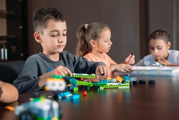 Crianças criando robôs com o professor.