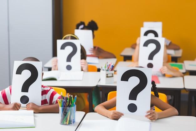Crianças da escola cobrindo seu rosto com sinal de interrogação