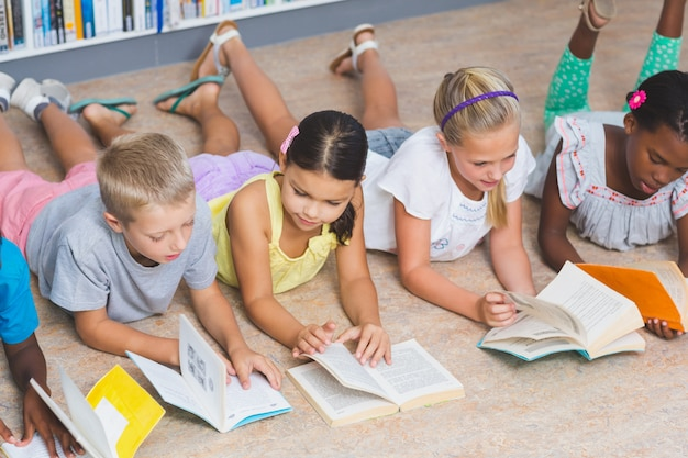 Crianças da escola, deitado no chão, lendo o livro na biblioteca