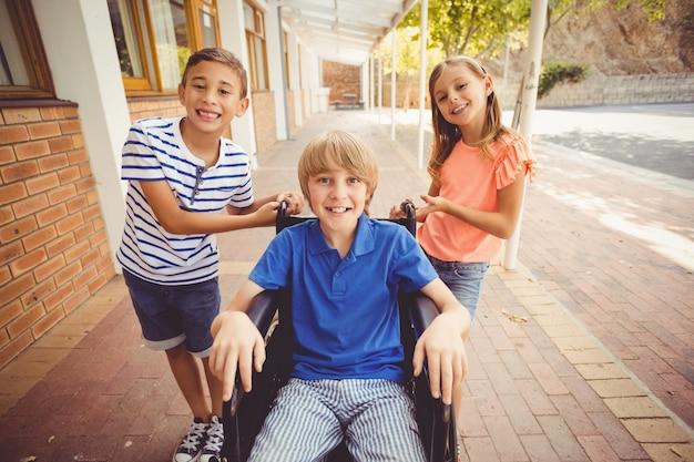 Crianças da escola empurrando um menino na cadeira de rodas